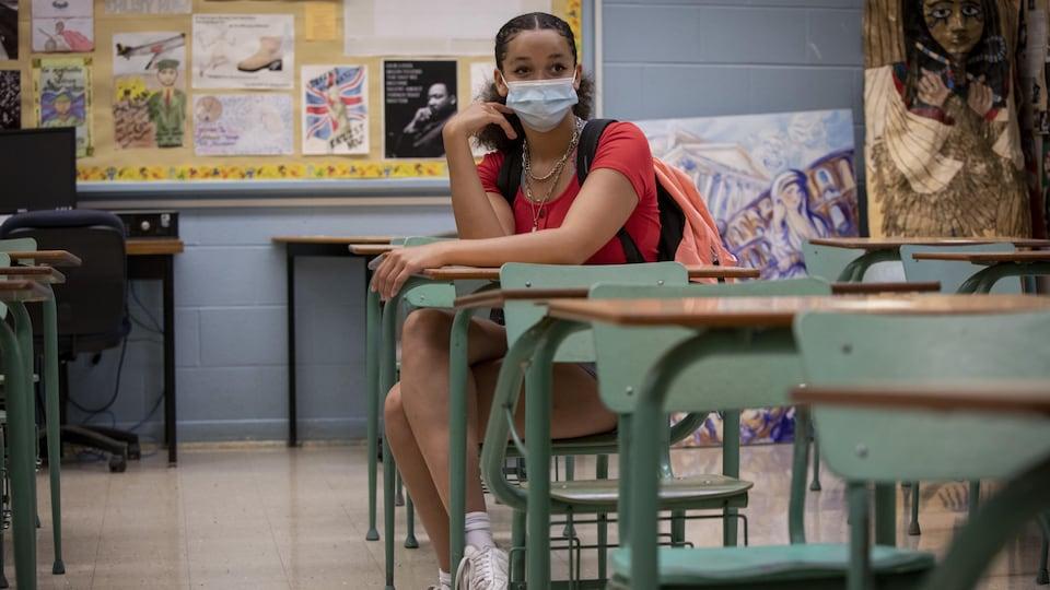 Une élève de l'école Wexford Collegiate School for Arts, à Toronto, est assise dans une classe vide. Elle porte un masque.