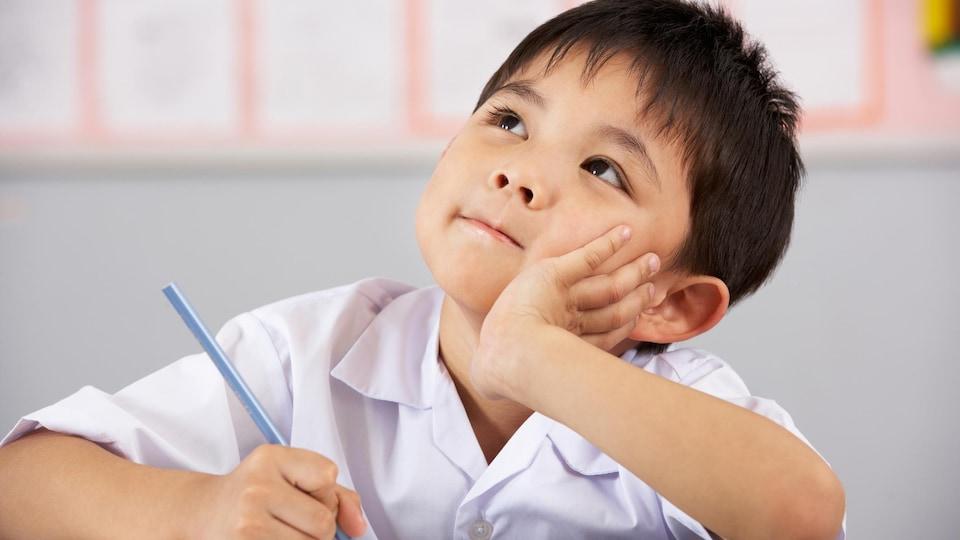 Un jeune étudiant du primaire rêvassant en classe.