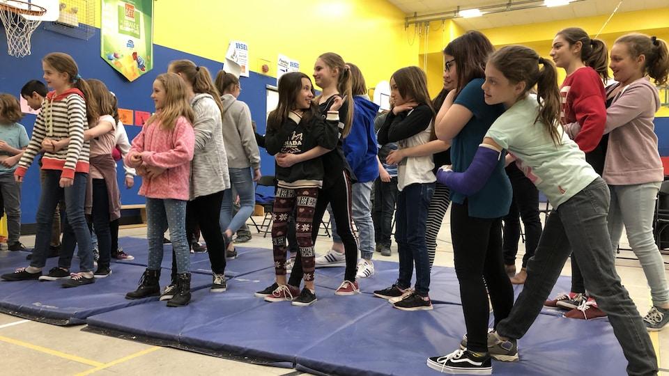 Des élèves pratiquent la technique à utiliser lorsque quelqu'un s'étouffe.