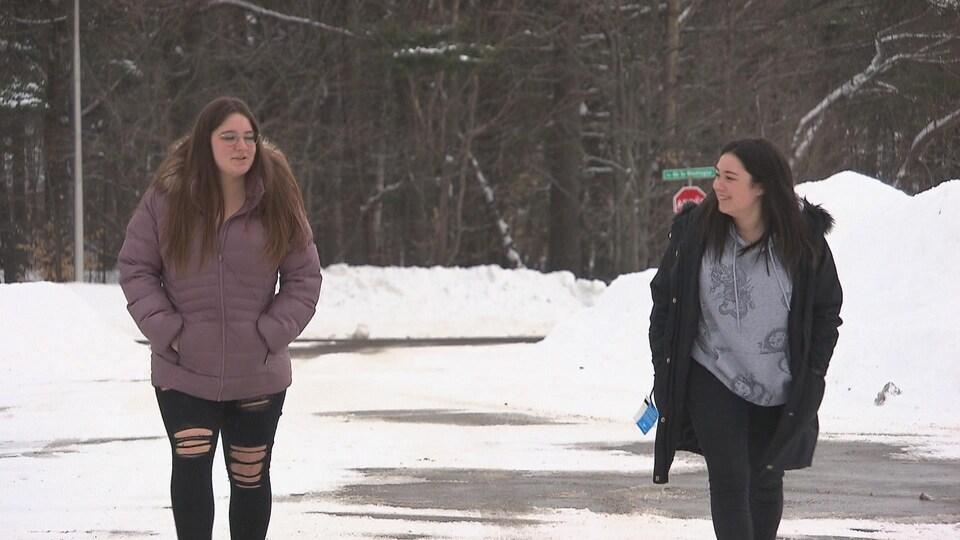 Deux jeunes femmes marchent à deux mètres de distance. Une porte un manteau mauve et l'autre a un manteau noir entrouvert.
