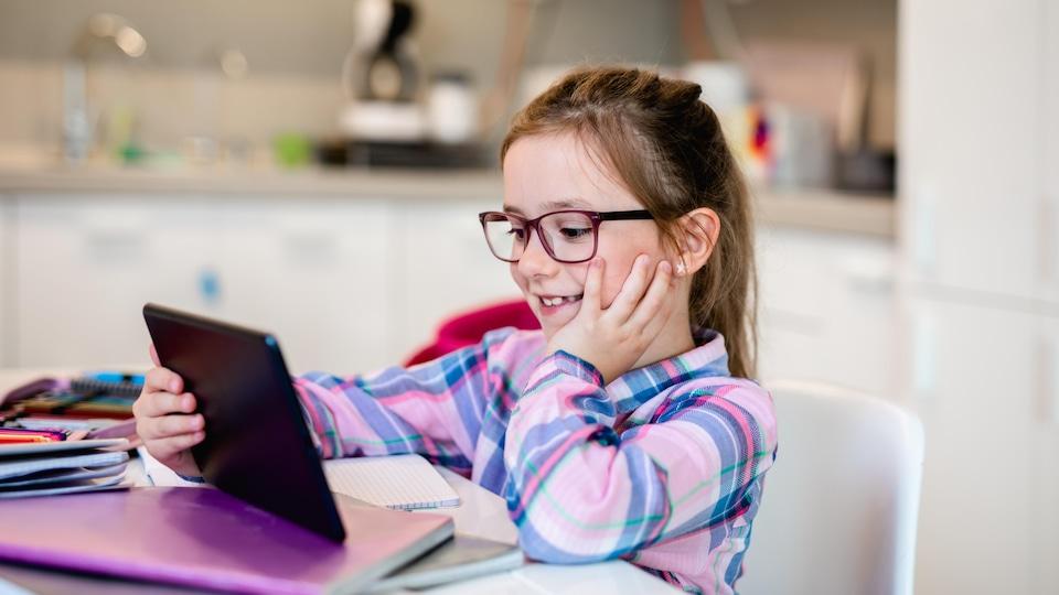 Une fillette fait des devoirs.