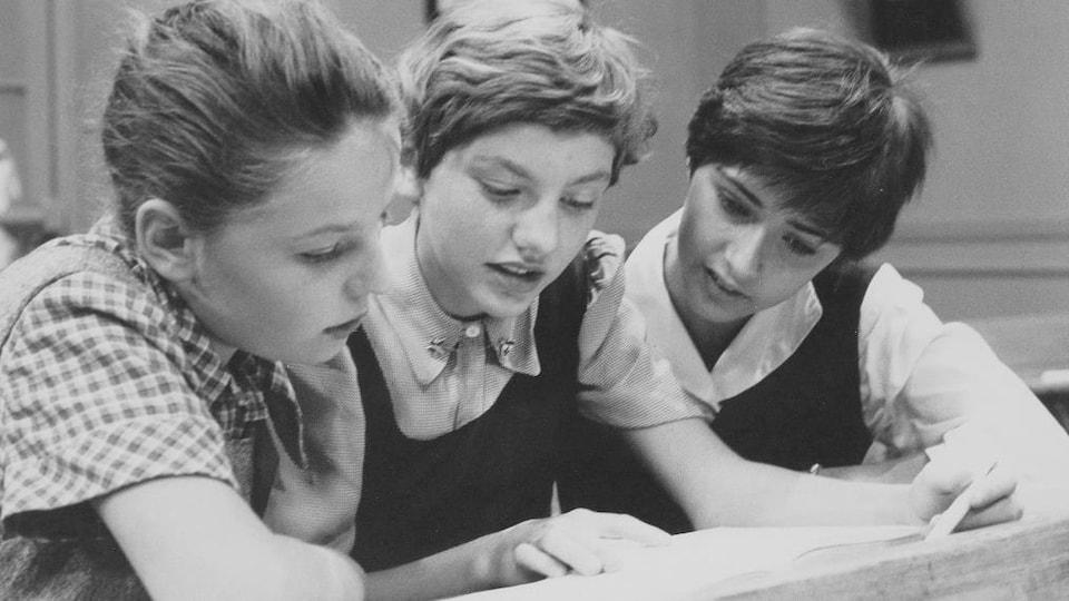 Trois élèves lisent un texte assises côte à côte à un bureau.