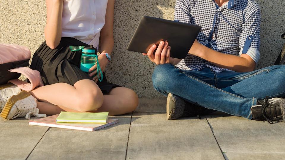 Une adolescente et un adolescent assis par terre le dos au mur tenant des livres et une tablette électronique.