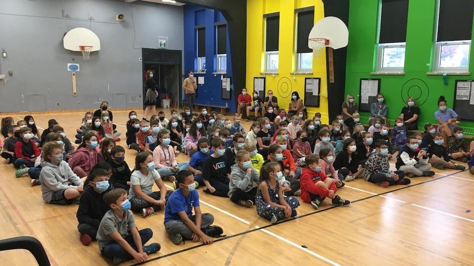 Des élèves assis en rang dans un gymnase.