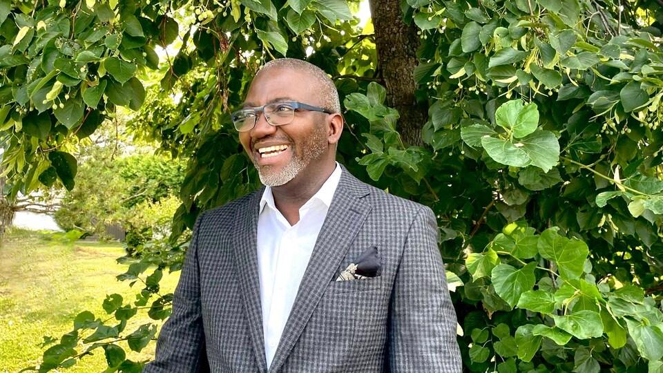 Un homme portant des lunettes sourit devant un arbre.
