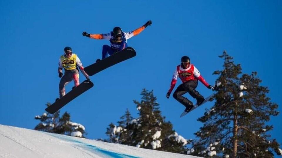 Trois planchistes sautent dans les airs