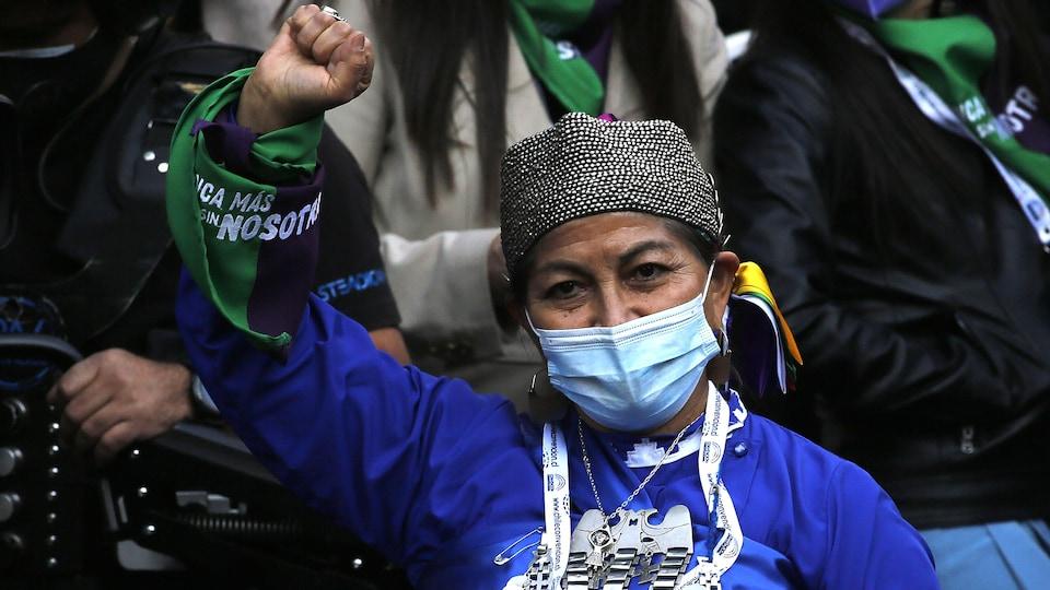 Une femme mapuche a le poing en l'air.