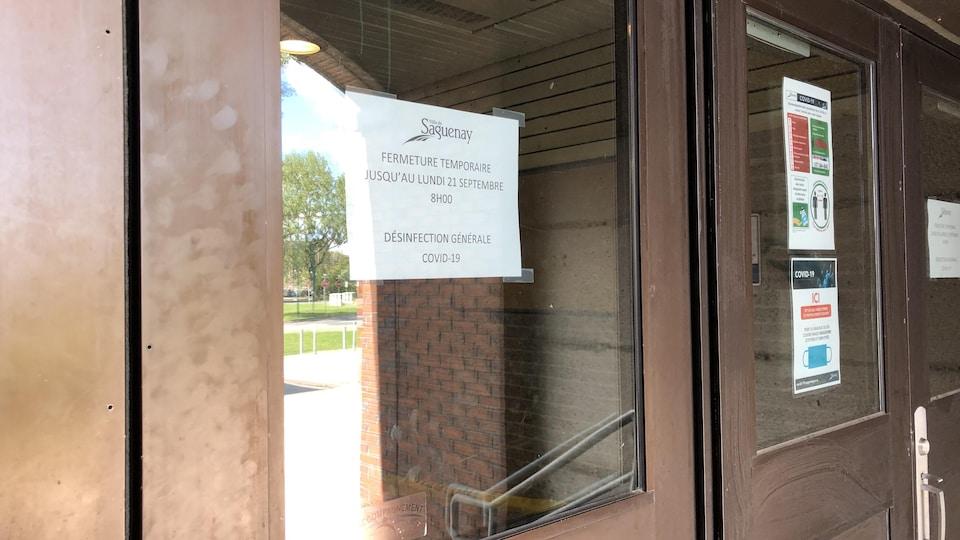 Une feuille indiquant une fermeture temporaire dans la fenêtre d'une porte.