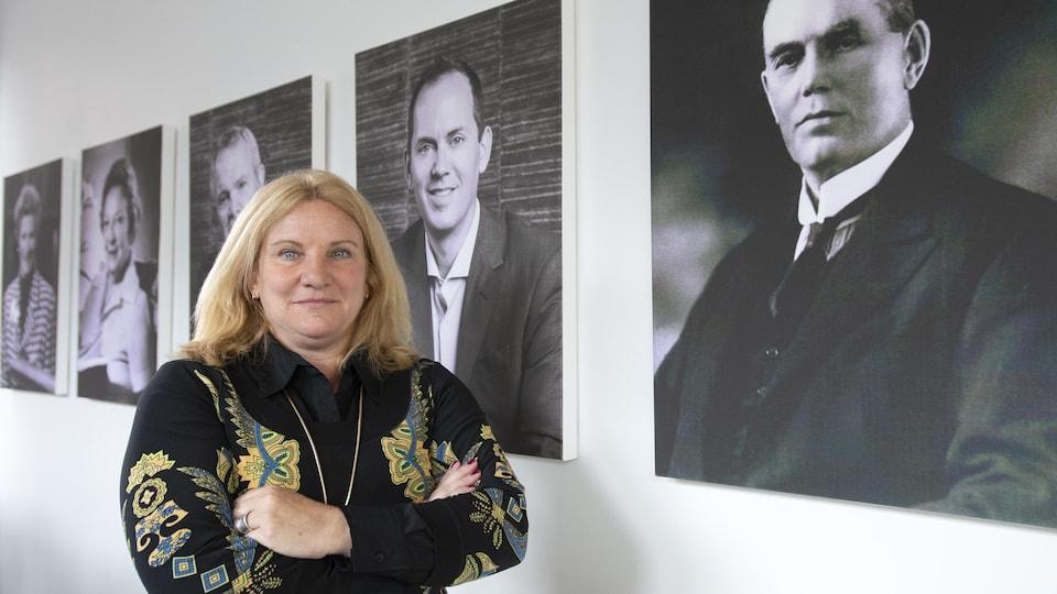 Elisabeth Ann Laett devant des portraits de la famille Holt, aux bureaux de l'entreprise The Holt Xchange.