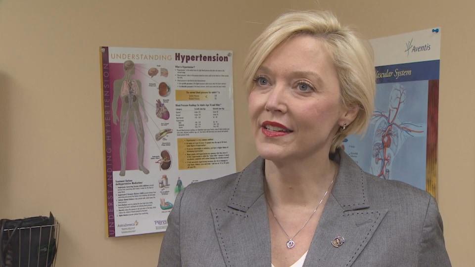 Elizabeth Smith-McCrossin devant une affiche sur l'hypertension.