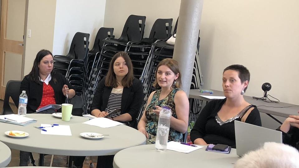 Une femme en train de parler à un groupe de personnes autour de tables rondes.