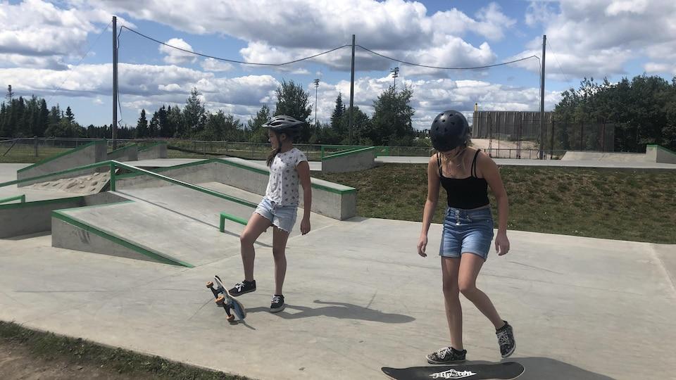 Deux jeunes filles se pratiquent sur une planche à roulette.