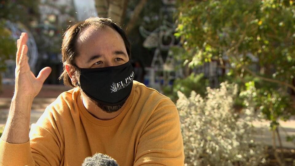 Un journaliste en entrevue avec un masque.