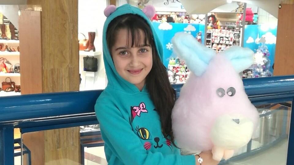 Une jeune fille avec une peluche sourit dans un centre commercial.