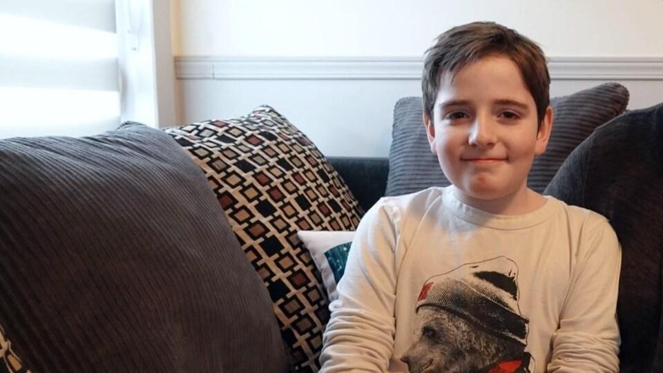 Elwan est assis sur un divan. Il porte un chandail avec un gros ours dessus. Il sourit.