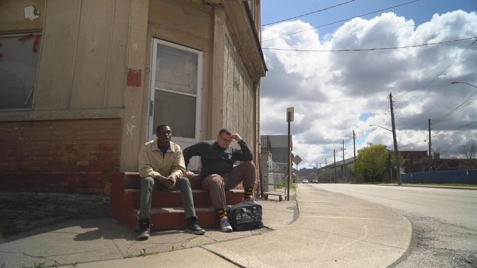 Deux jeunes hommes assis sur les marches d'une maison délabrée