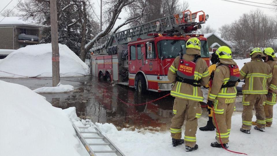 Des pompiers discutent devant un camion à échelle dont l'arrière est enfoncé dans l'eau.