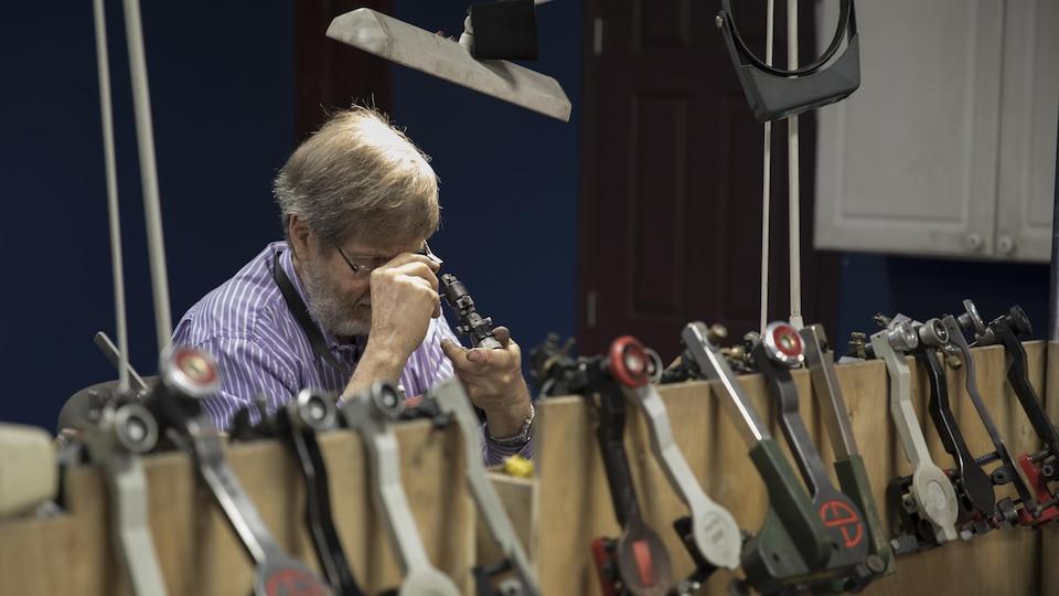 Un homme examine un diamant à l'aide d'une loupe.  Plusieurs instruments sont accrochés sur le bord d'un bureau.