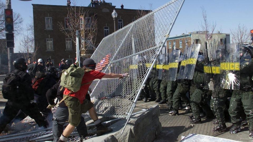 Des manifestants tentent de renverser une section d'une clôture grillagée sous le regard de policiers antiémeute.