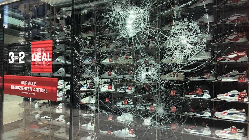 Une vitrine d'un magasin de chaussures de sport présente quatre impacts, mais a toutefois tenu le coup face aux assauts.