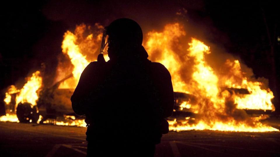 Un agent de la brigade anti-émeute regarde deux voitures de police brûler lors des émeutes au centre-ville de Vancouver, le mercredi 15 juin 2011, à la suite de la défaite 4-0 des Canucks de Vancouver contre les Bruins de Boston lors du septième match de la finale de hockey de la Coupe Stanley.