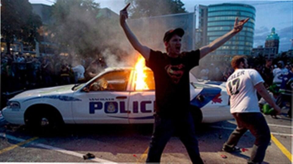 Un homme s'agite devant une voiture de police en feu.