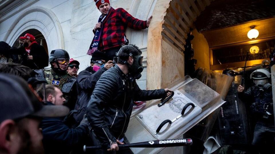 Des manifestants tentent de faire intrusion dans le Capitole, usant de violence pour pénétrer dans l'édifice, que tentent de défendre des policiers.