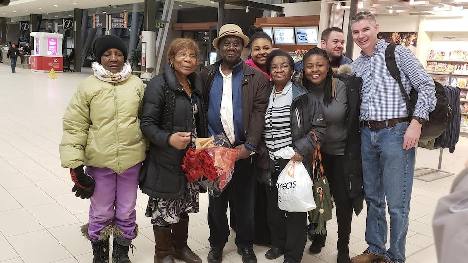 Un homme de race noire avec un chapeau entouré d'hommes et de femmes.