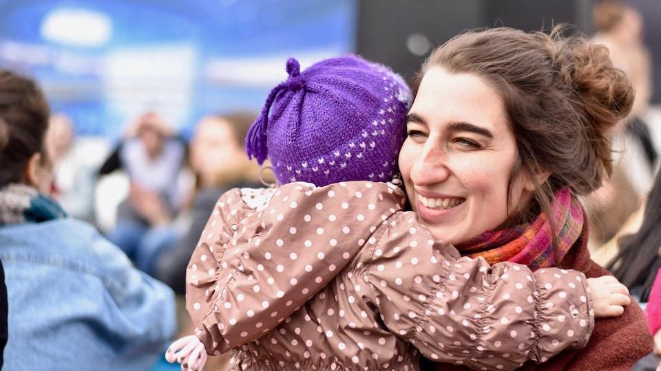 Émilise Lessard-Therrien serre dans ses bras un enfant qu'on voit de dos.