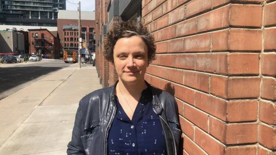 Emily Alfred pose dans une rue de Toronto, elle porte une petite veste en cuir et une chemise bleue marine, elle a les cheveux courts et un peu poivre et sel, elle a léger un sourire