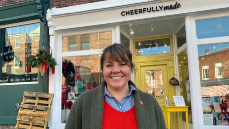 Emily Arbour devant la porte jaune et les vitrines de son magasin.