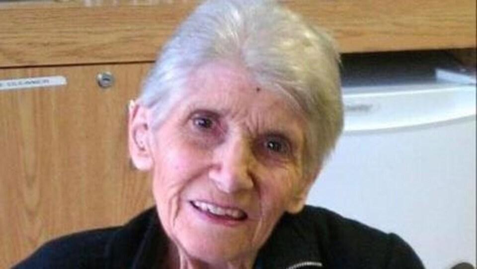 Une femme âgée est assise devant un gâteau au chocolat en forme de hibou.