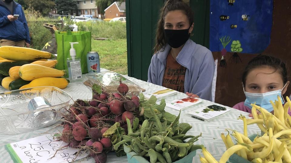Emily McPhee devant une table de légumes.