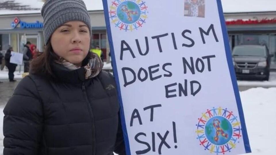 Emily Sheridan à l'extérieur. Elle tient une pancarte sur laquelle on peut lire «Autism Does Not End At Six!»