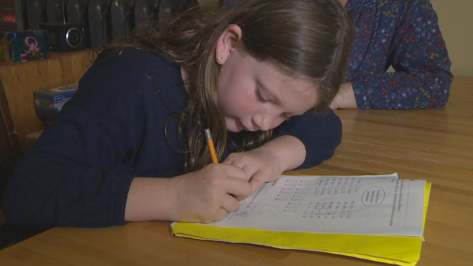 Une fillette fait ses devoirs