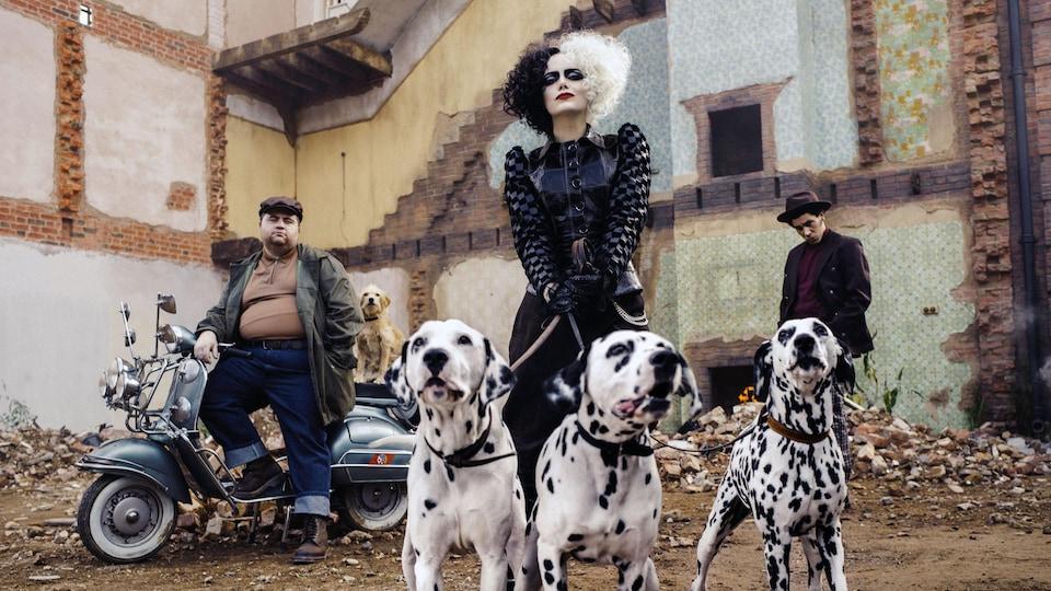 Emma Stone tient trois chiens dalmatiens avec deux hommes en arrière-plan.