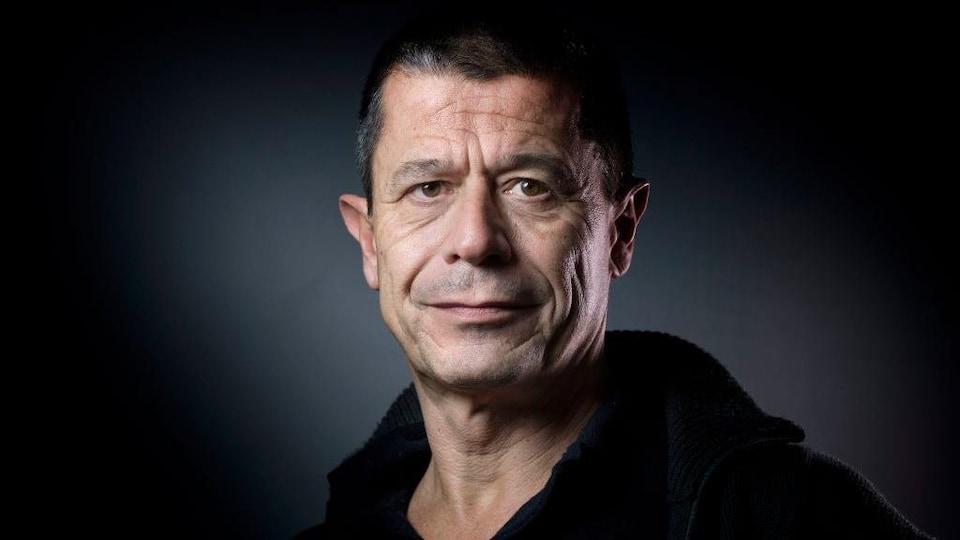 Portrait d'Emmanuel Carrère qui fait un demi-sourire.