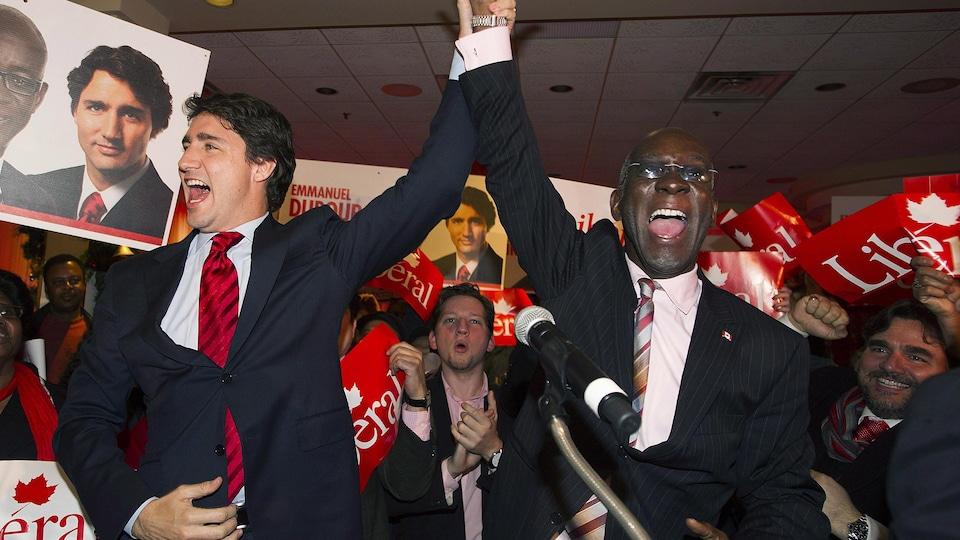 Le chef libéral Justin Trudeau lève le bras du député élu Emmanuel Dubourg pour célébrer sa victoire.