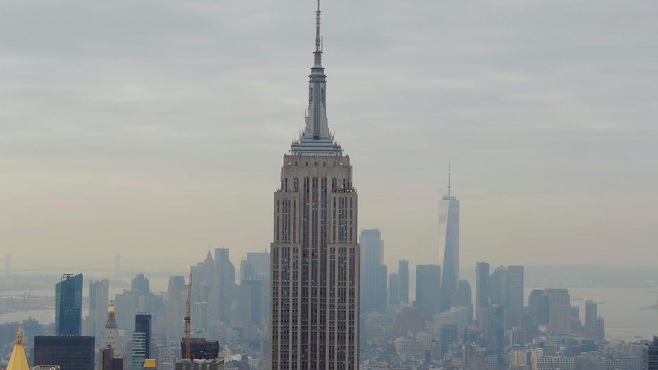 La partie supérieure de l'Empire State Building vue dans les airs avec la ville de New York en arrière-plan.