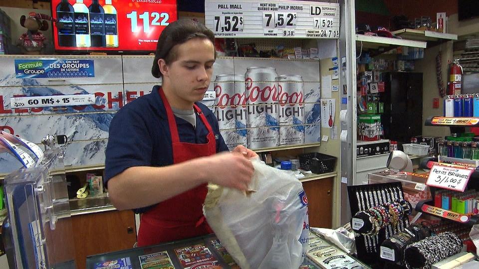 Un employé place les achats d'un client dans un sac de plastique.