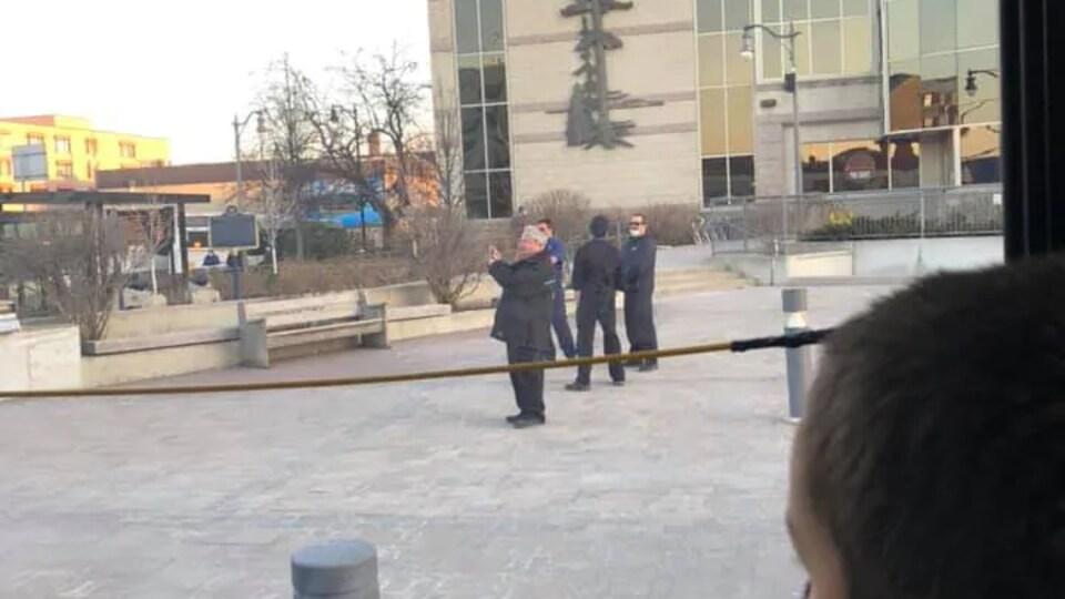 Un groupe d'hommes devant l'hôtel de ville de Thunder Bay