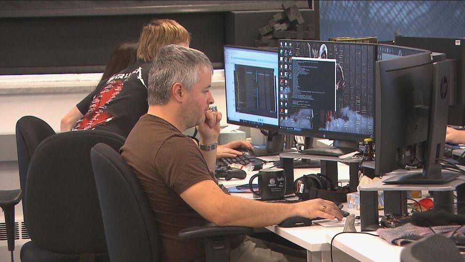 Trois employés regardent des écrans d'ordinateur dans un espace de travail commun.