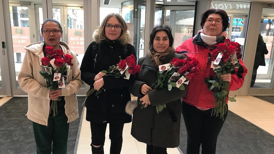 Quatre femmes qui tiennent des roses rouges dans leurs mains.