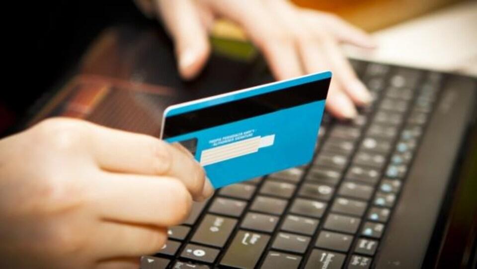 Une personne fait un achat en ligne devant son ordinateur.