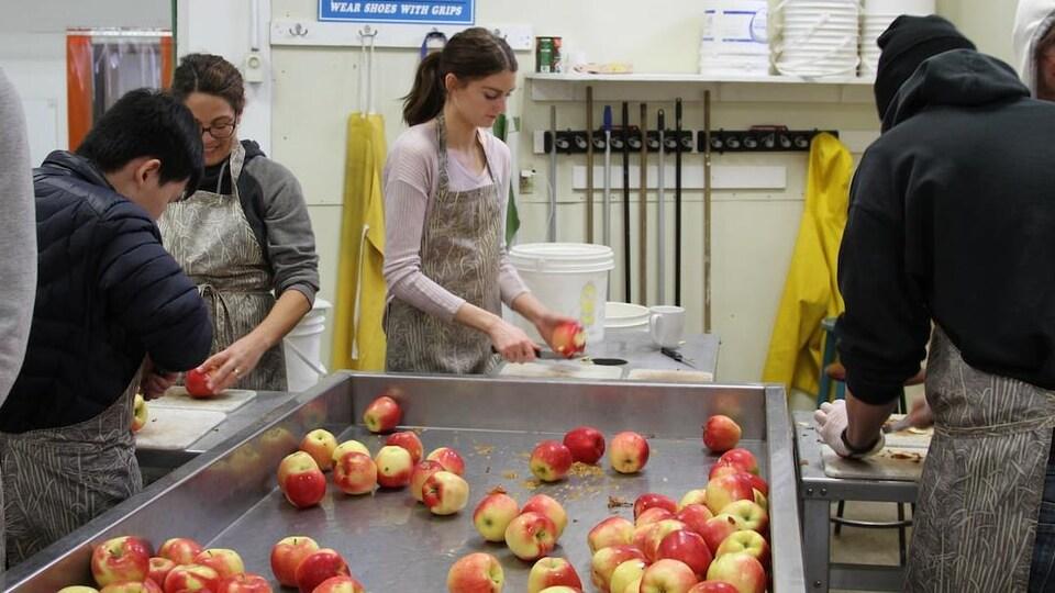 Des étudiants coupent des pommes dans une cuisine industrielle.