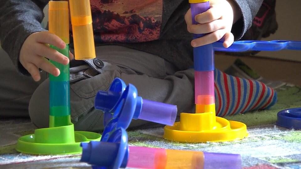 On voit seulement les mains et les jambes de l'enfant derrière le jouet.