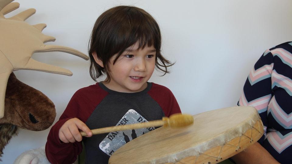 Un enfant avec un tambour dans les mains.