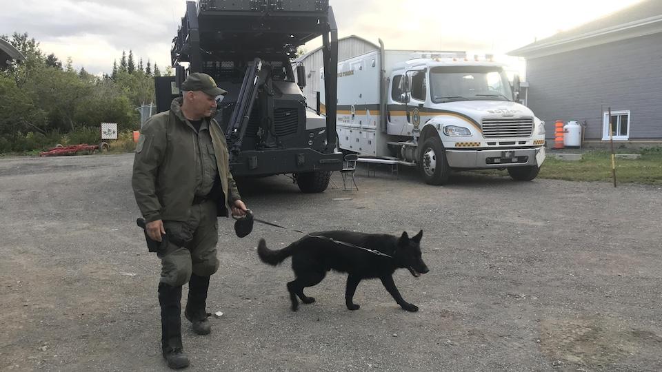 Un maître-chien tient son animal en laisse.