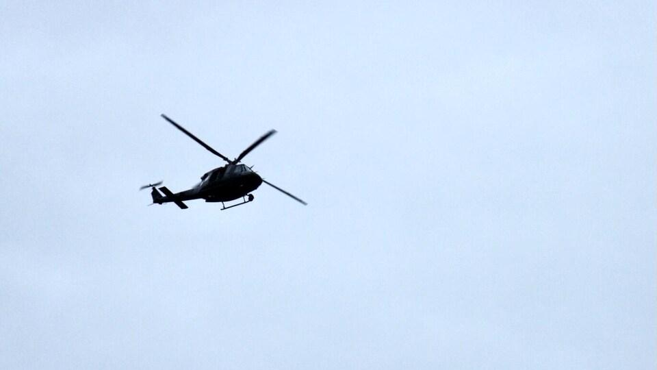 Un hélicoptère en vol dans un ciel bleu.