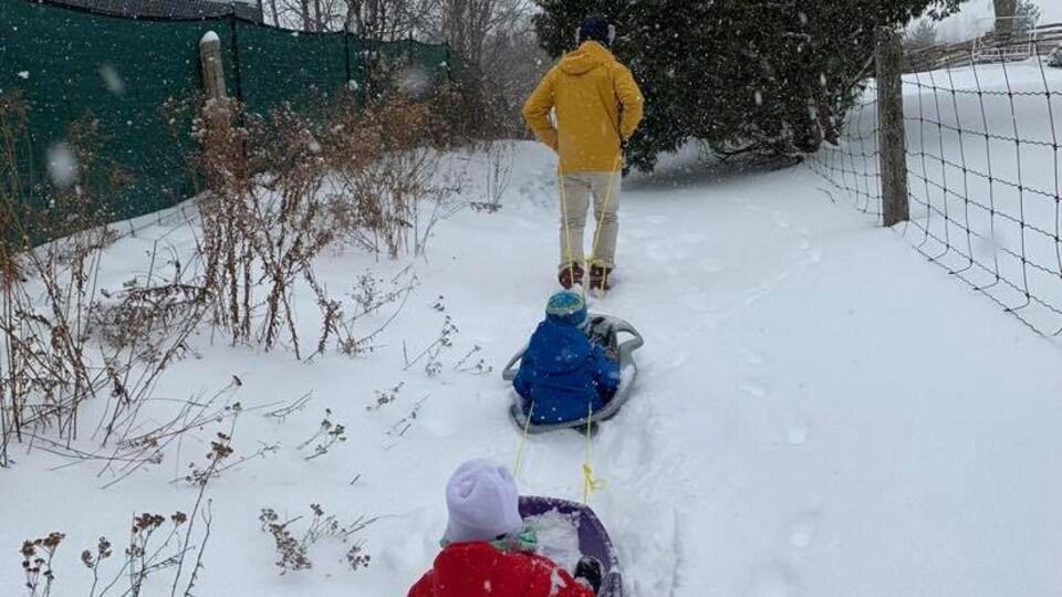 Un adulte tire deux jeunes enfants dans leur traîneau sur un sentier enneigé.